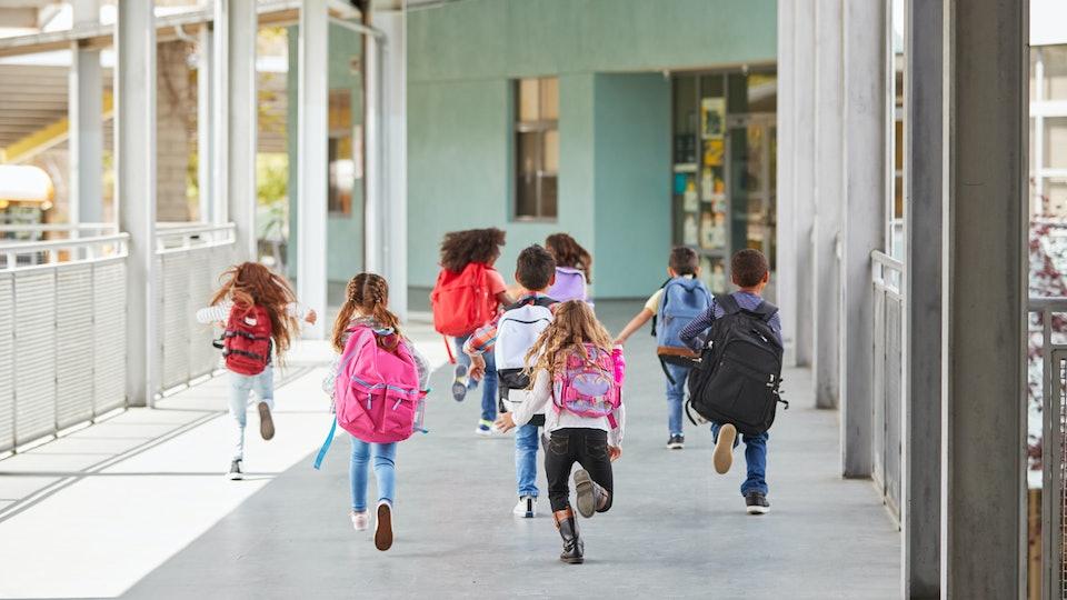 Elementary school kids run from camera in school corridor