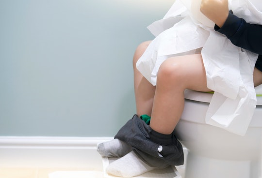 School kid sitting on toilet and playing with toilet rolls, Low view on his legs hanging with grey trousers with fluffy socks,Child tearing the tissue, copy space,Training child or Health care concept