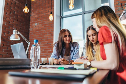 Group of female coworkers working on new project sitting at desk in creative office