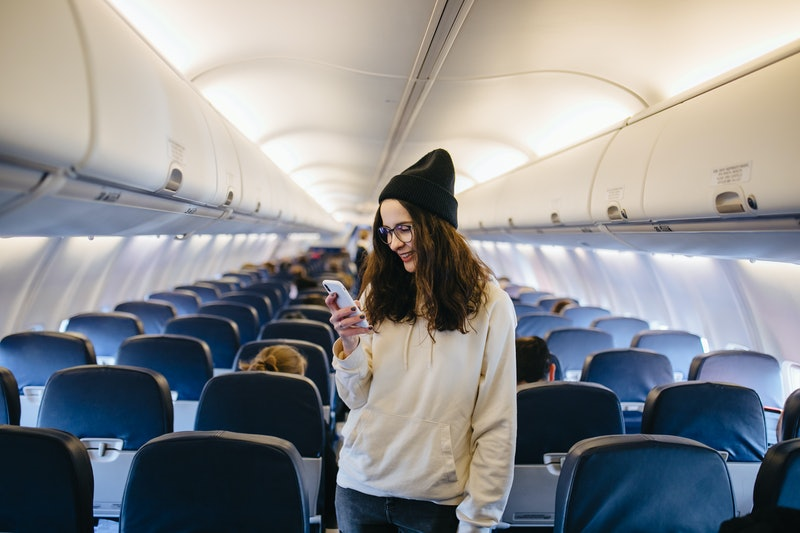 Beautiful girl in glasses and hat sitting on the seat in the airplane and making selfie. Traveler smiles in the aircraft.