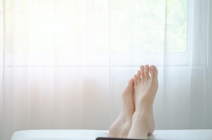 Women's feet are placed on the sofa in the bedroom. Relaxing concept on a relaxing day.Do not focus on the main object of this image.