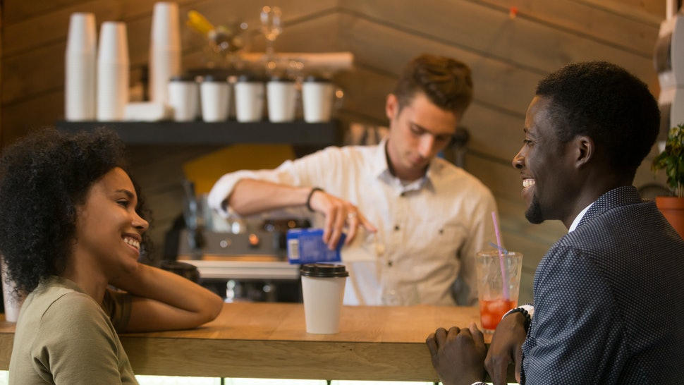 African american man and woman flirting talking at bar counter, black couple enjoying drinks and pleasant conversation on first date in cafe, young guy with lady having fun at meeting in coffee house
