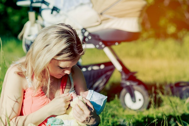 Girl is breastfeeding in nature. Copy space