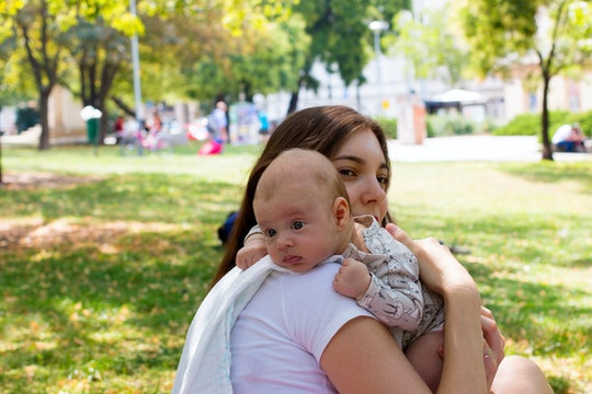 Portrait of the mother and child, little baby resting head on the mom's shoulder, burping position after breastfeeding, family is sitting on green grass and enjoying beautiful sunny day in the park