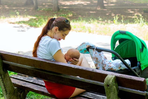 Parent nursing infant, pretty mother is gently caring her little baby in the hands, embracing him softly with love and breastfeeding outside in the park covered by sun light, stroller walking stop