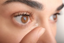 Young woman putting contact lens in her eye, close up view. Medicine and vision concept