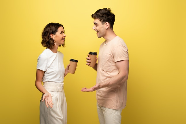 smiling man and woman talking while holding paper cups on yellow background