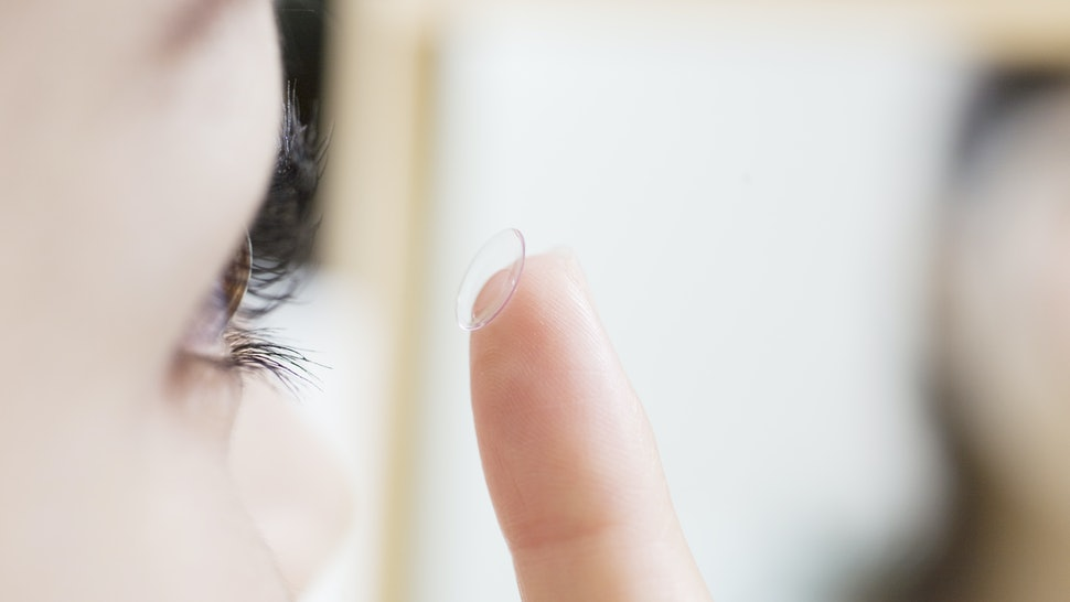Japanese women trying to put contact lenses on an eye