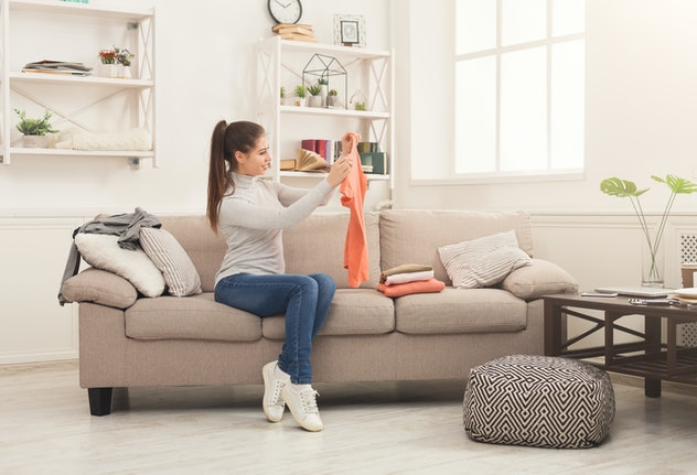 Woman folding clean t-shirts, sitting on sofa at home. Young girl tidying up clothes after laundry o...