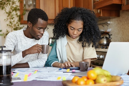 Finances and family budget concept. Indoor shot of serious African girl using calculator while payin...