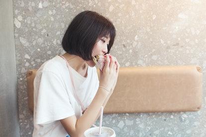 Girl having fun eating burger in restaurant