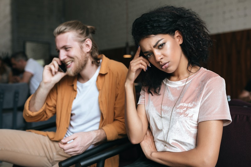 Portrait of young man and girl sitting in restaurant. Upset African American girl with dark curly hair sadly looking in camera while boy with blond hair happily talking on his cellphone at cafe