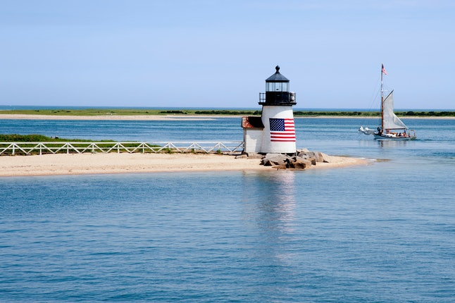 Sailing past Brant Point lighthouse on Nantucket Island on a warm quiet summer day in New England. American flag drapped on lighthouse tower.