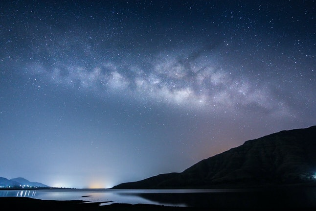 Landscape with blue Milky Way. Night sky with stars, mountains, lake.