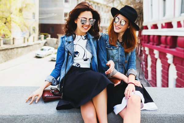 Close up  summer lifestyle portrait of two best friends laughing and talking  outdoor on the street in city center . Wearing stylish jeans jacket , dress, sunglasses.