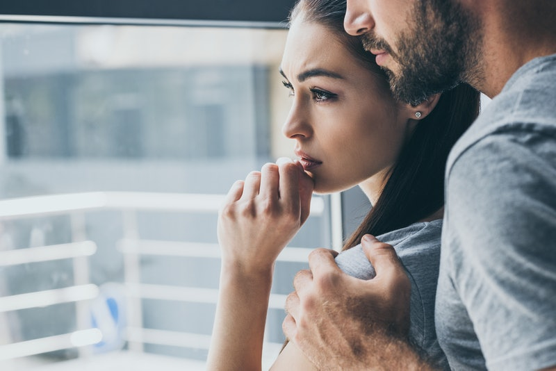 cropped shot of bearded man supporting sad young woman looking at window