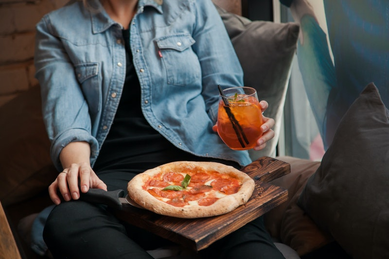 Woman with pizza and coctail