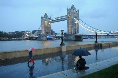 Tower Bridge people with umbrellas in London, United Kingdom