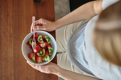 Pregnant woman eating a bowl of fruit salad with fresh strawberries seated at a dining table in a close up on the food and her belly in a healthy diet concept