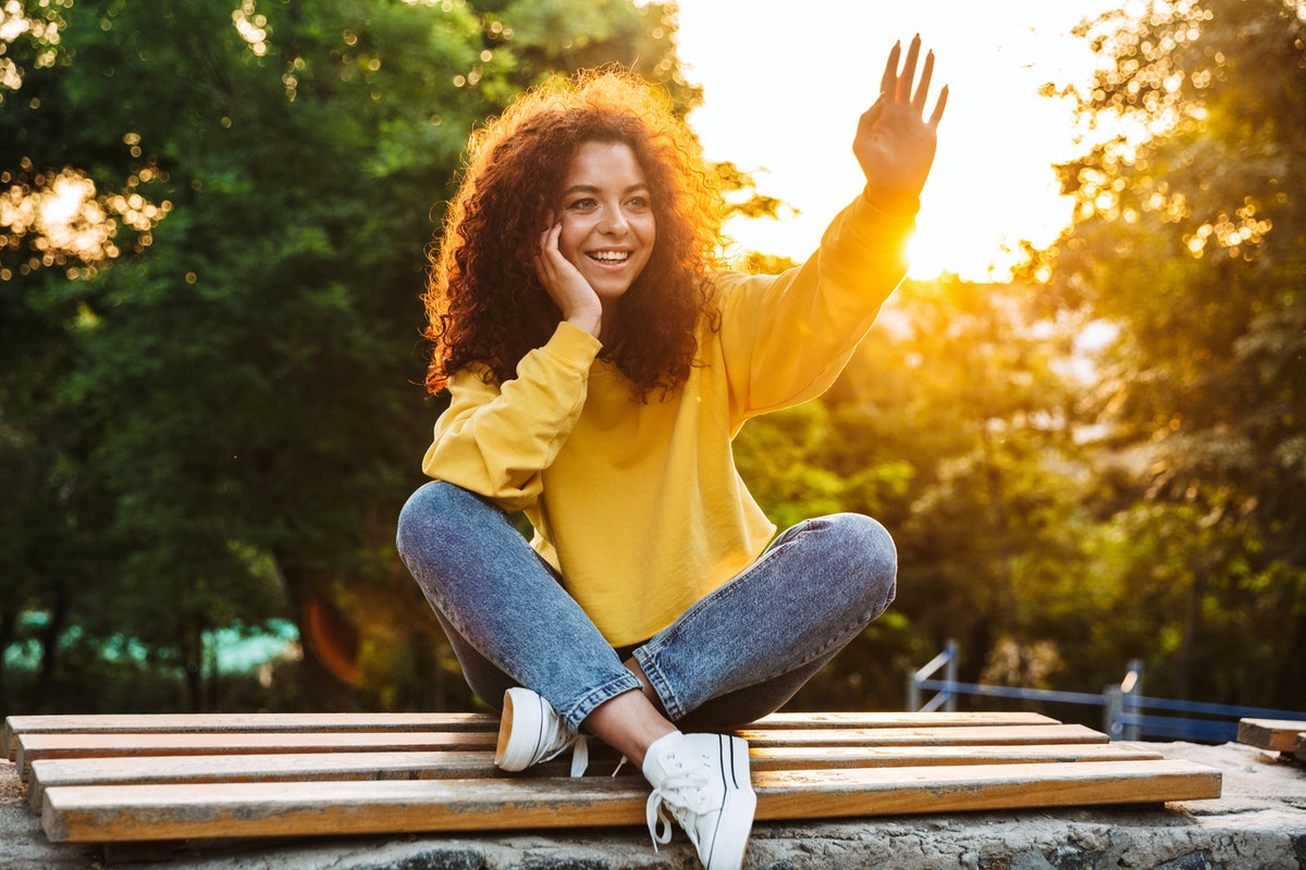 Photo of a happy cute young student curly girl sitting on bench outdoors in nature park with beautiful sunlight looking aside waving to friends.