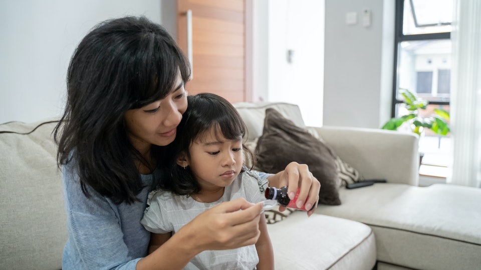 asian mother giving her daughter a medicine at home
