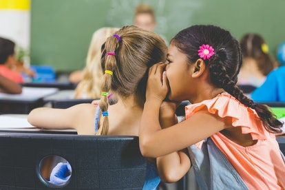 Schoolgirl whispering into her friend s ear in classroom at school