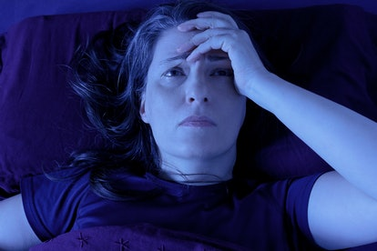 Middle aged woman lying awake in her bed at night because of insomnia, stress, fears, nightmares or illnesses like fibromyalgia