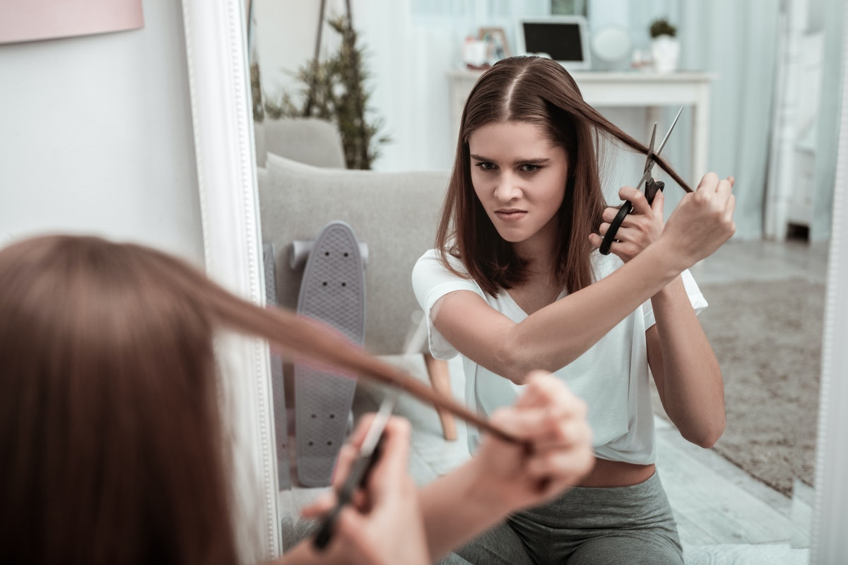 Self-made haircut. A woman attempting to cut her hair herself