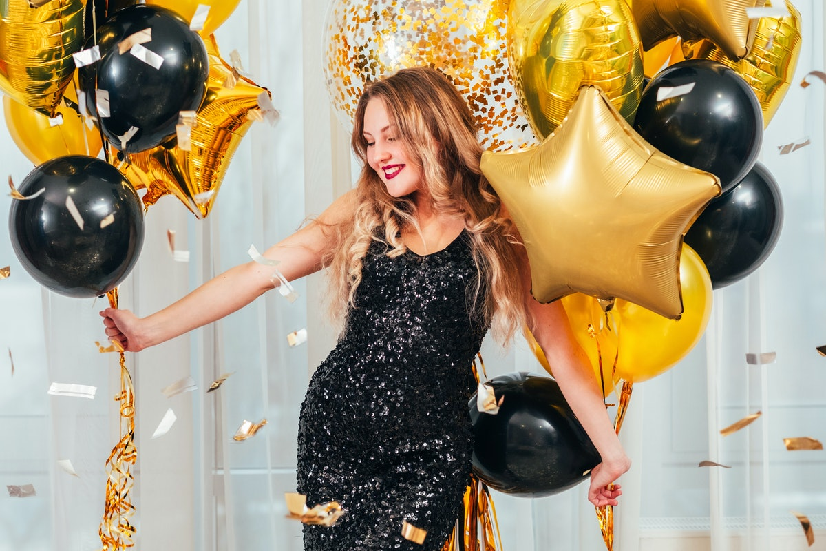 Birthday party. Happy girl in black sequin dress standing in white room with balloons. Pretty lady smiling, enjoying celebration.