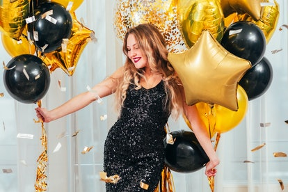 Birthday party. Happy girl in black sequin dress standing in white room with balloons. Pretty lady s...