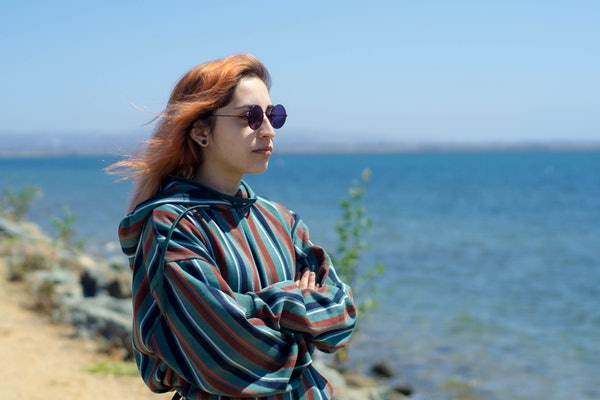 serious hip woman staring into the ocean