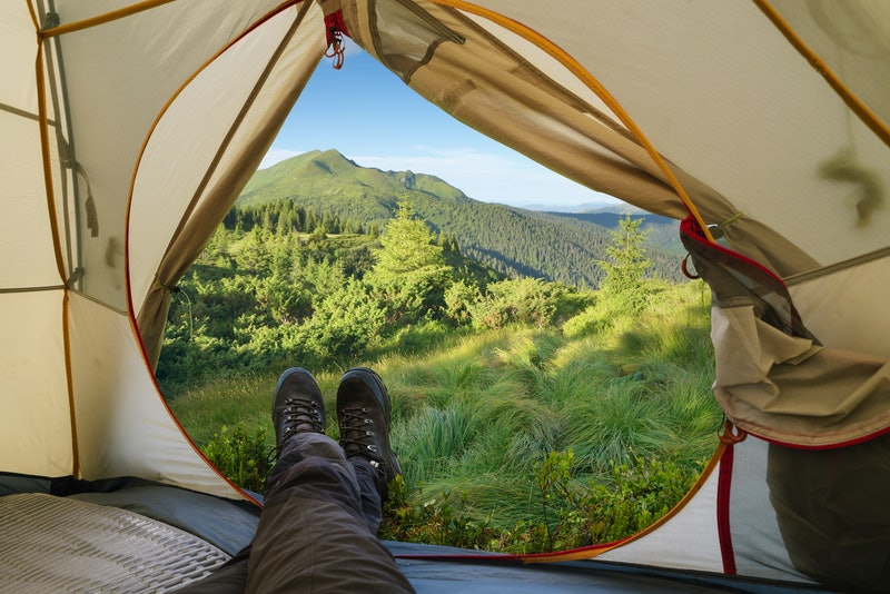 Camping in the mountains. Summer hike. View from a tourist tent on a peak. Guy in trekking boots
