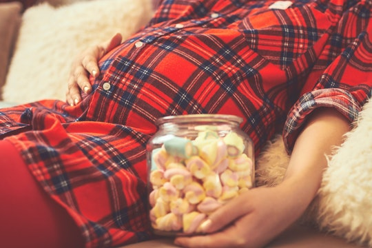 Pregnant woman eating candy. Focus on belly.
