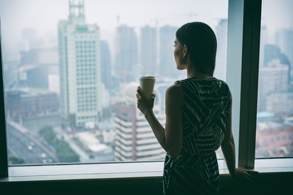 Businesswoman drinking coffee at work contemplative looking out the window of high rise skyscraper b...