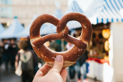 A girl or a young woman is holding a traditional German pretzel in the street. Oktoberfest festival in the background.