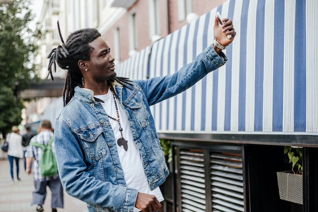 Tourist African guy takes a selfie on the phone standing on the street of the city