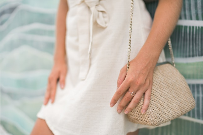 Woman in beige dress with small bag and moon ring on hand