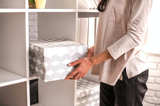 Woman put a cardboard box on shelf. Concept of organization of work space.