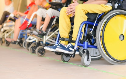 Disabled children sitting in wheelchairs, In line to wait for activities ,Close-Up yellow wheel, Lif...