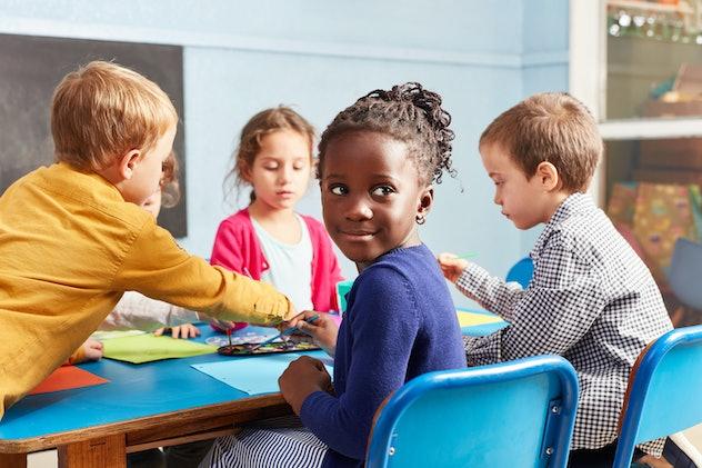 Group of kids or preschoolers together in painting class in kindergarten or preschool
