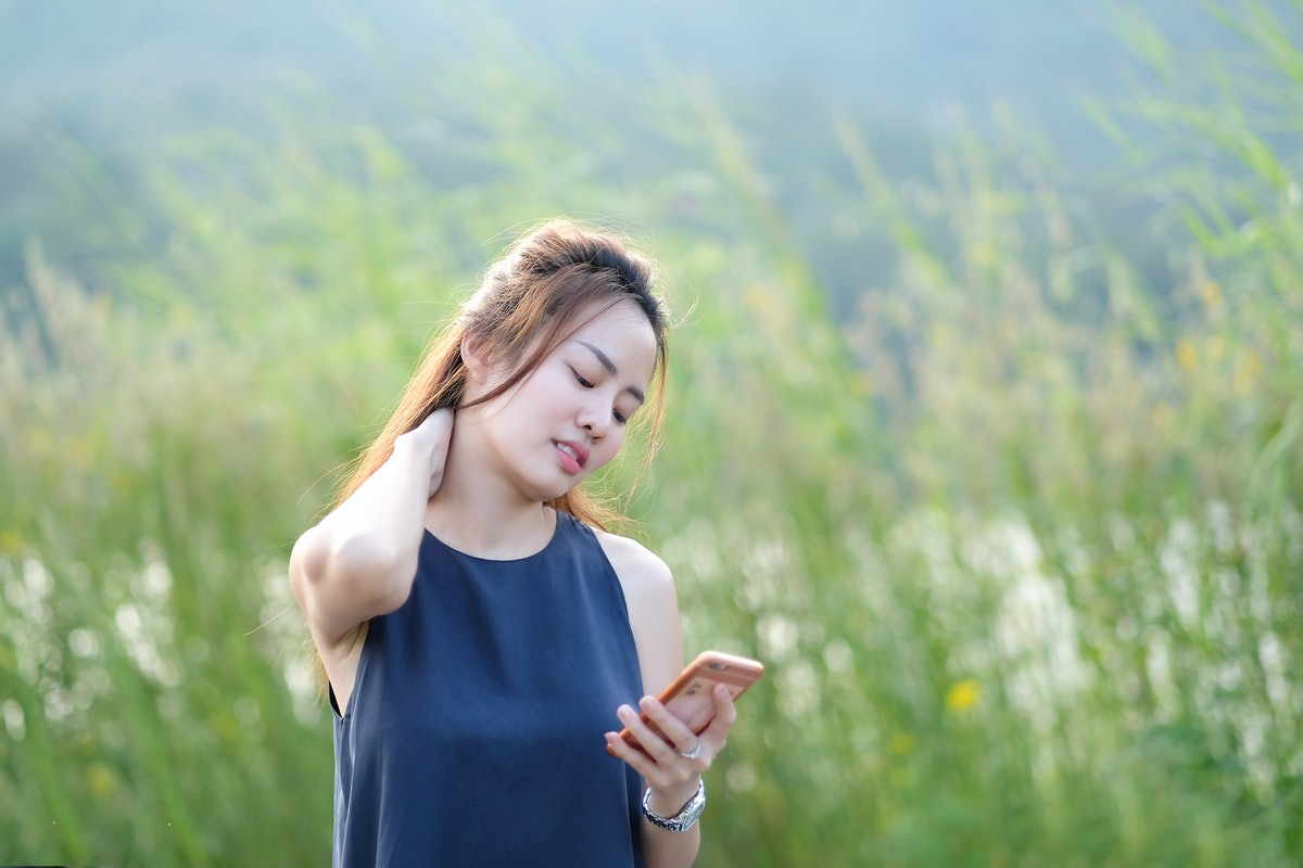 beautyful Asian woman use hand massaging her neck. Symptoms of Text Neck Syndrome.