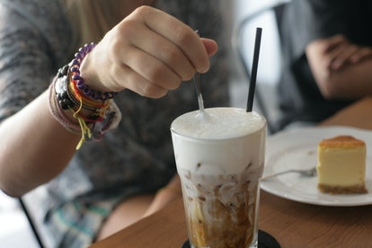 Woman stirring iced coffee in focus