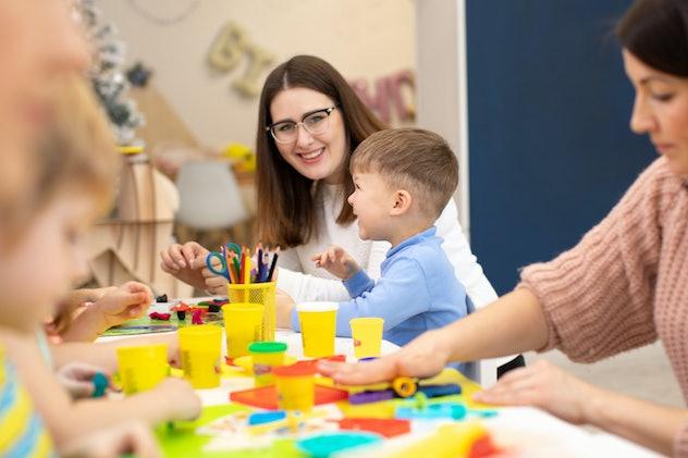 Preschool kids sticking with plasticine in classroom in kindergarten