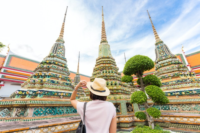 Adventure Asian beautiful tourist women travel in the buddha temple back view in Bangkok Thailand