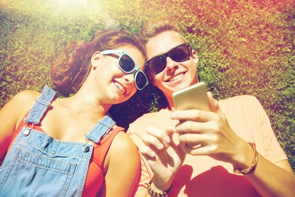 love and people concept - happy teenage couple in sunglasses with smartphone lying on grass at summe...
