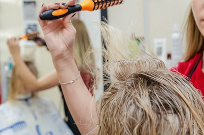 Hair styling a hair dryer for a blonde girl