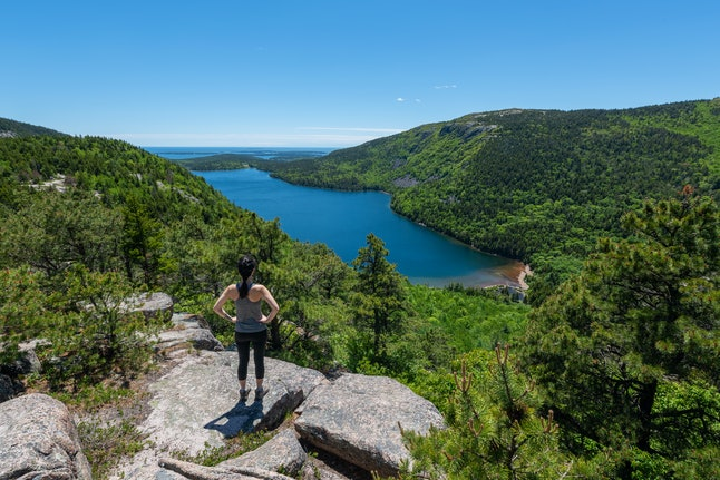 Female hiker reaching the top of an overlook of Jordan Pond at Acadia National Park