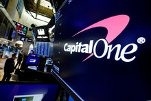 The logo for Capitol One Financial appears above a trading post on the floor of the New York Stock E...
