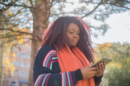 Cute smiling woman is reading pleasant text message on tablet pad while sitting in the park in warm ...