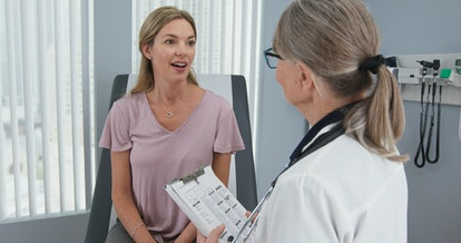 Over the shoulder shot of woman talking to her primary care doctor in exam room. Middle-aged patient having appointment with female senior physician